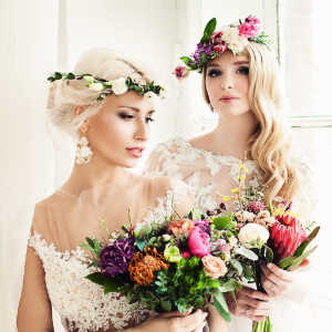 Two Beautiful Blonde Women Fiancee. Fashion Model with Flower Arrangement, Flower Wreath, Wedding Hairstyle and Makeup
